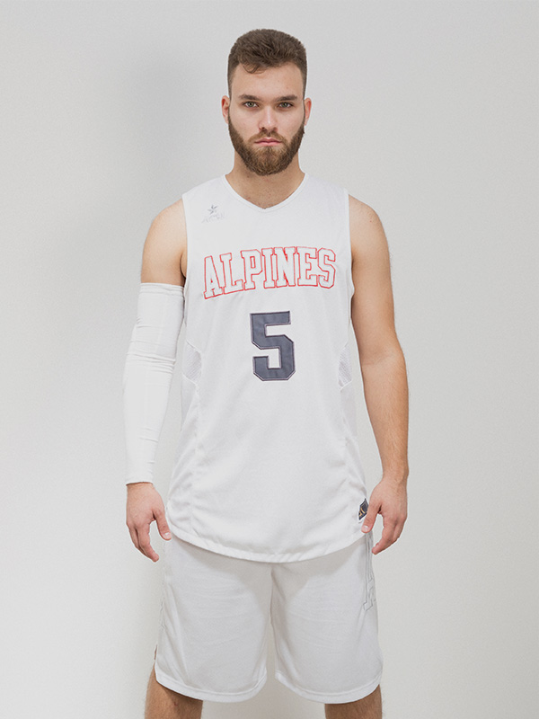 Male model wearing a white sleeveless basketball jersey, white shorts, and a white arm warmer on his right arm.