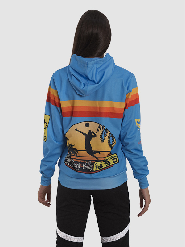 A female model wearing a blue, dye sublimation printed polyester custom-made hoodie. The back side of the hoodie is shown.