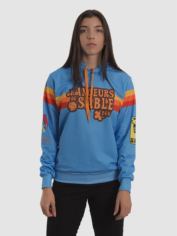 A female model wearing a long-sleeved all-over sublimated blue sweatshirt with red, orange, and yellow stripes printed over the chest area.
