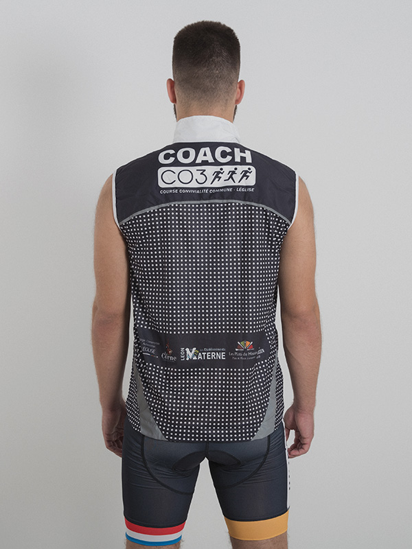 A made model wearing a grey and black custom-made running west with the white logo printed on the back. Back side is shown.