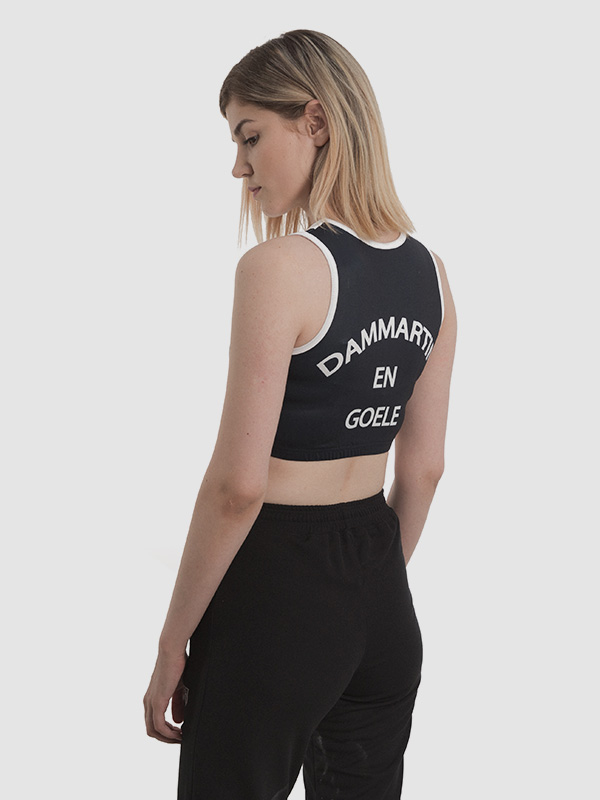 A female model wearing a black and white running crop top. Back side is shown.