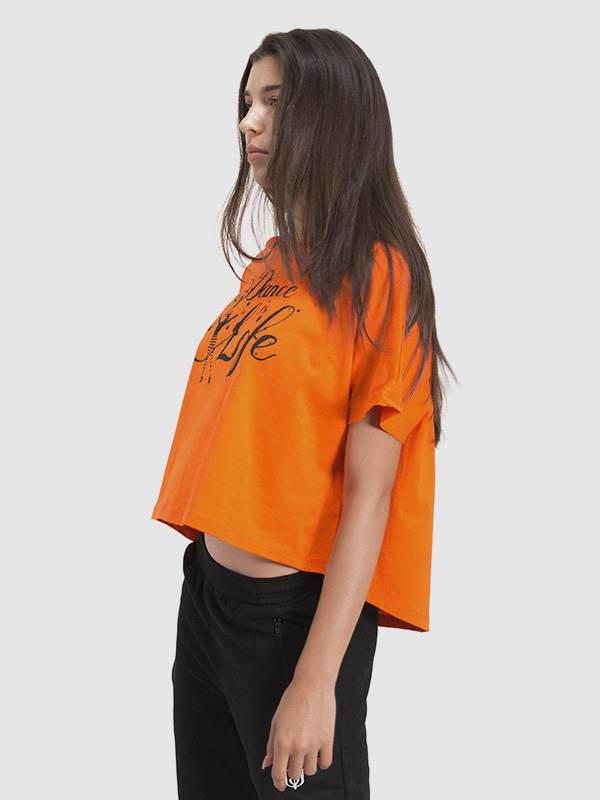 A female model wearing an orange zumba t-shirt. Left side is shown.