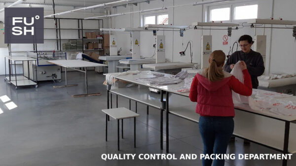 Photo of the quality control and packing department taken in FUSH's Oraovica factory in South-Eastern Serbia. In the foreground, two workers are packing the clothes.
