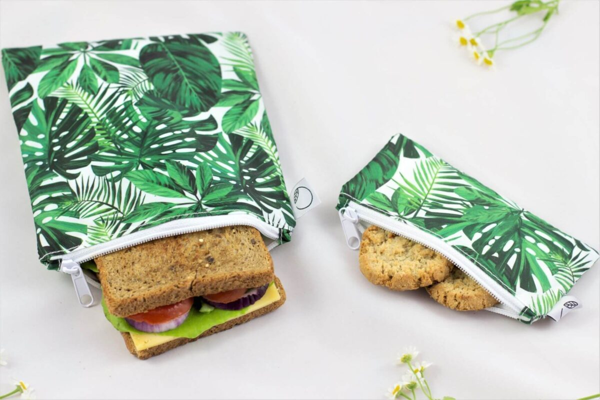 2 reusable snack bags, one big, one small. There is a sandwich in one snack bag and cookies in another.