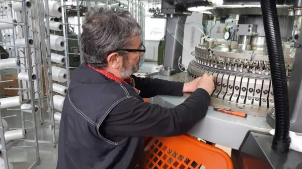 A man operating a circular kniting machine at a factory of activewear manufacturers.