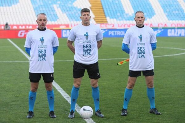 Three football referees standing in the center of the football pitch.