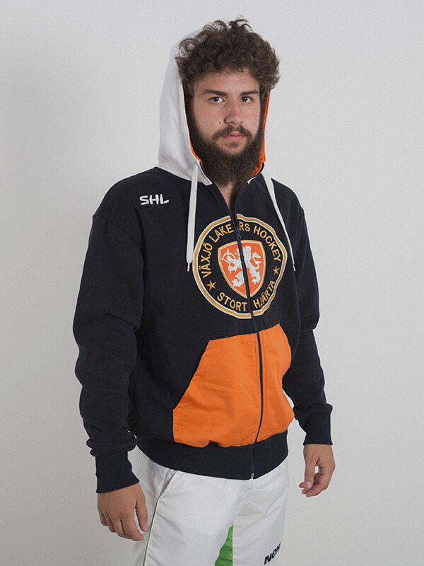 A male model wearing a black zipped hoodie with a gray hood and gray drawstrings and orange pocket area. Logo of a hockey team is embroidered in the chest area.