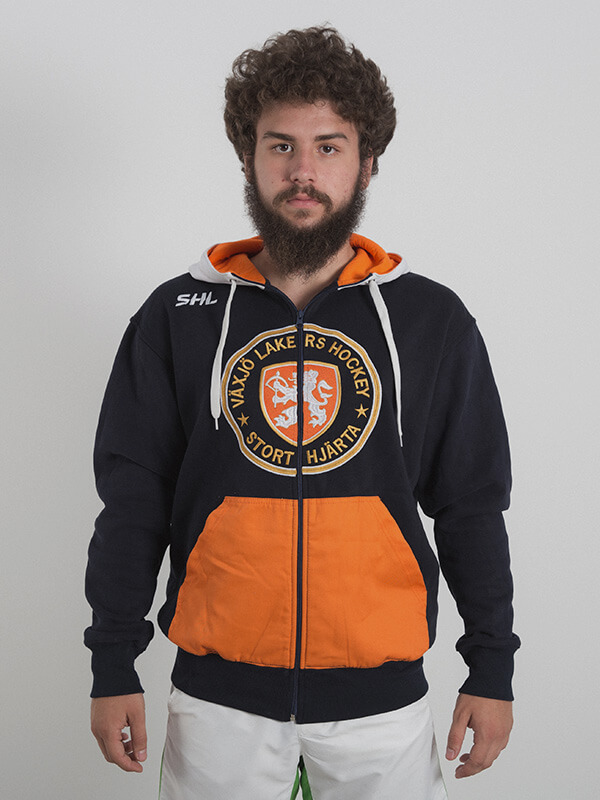 A male model wearing a black zipped hoodie with gray drawstrings and orange pocket area. Logo of a hockey team is embroidered in the chest area.
