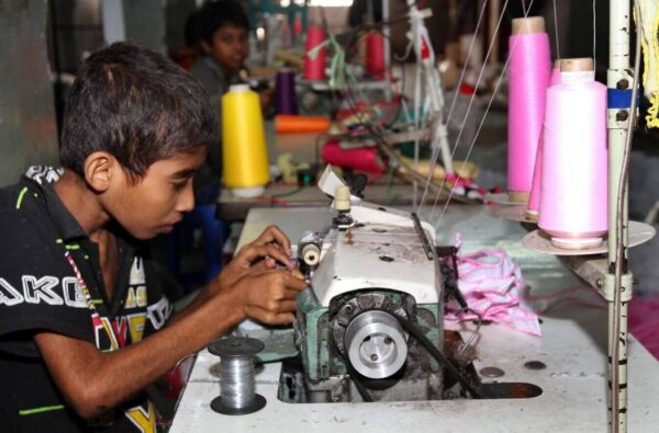 A child working at the sewing machine in a garment factory. Another child worker is seen in the background.