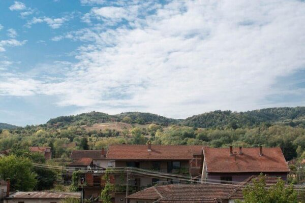 Houses at the foot of the hill and the white scattered clouds can be seen in this image.
